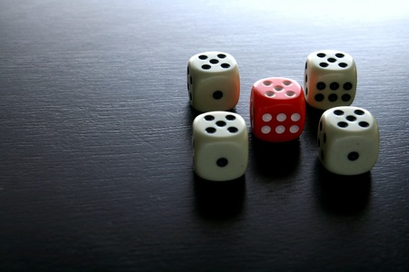 black white red: One Red game dice among several white game dice Stock Photo