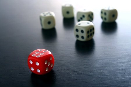 top 7: One Red game dice in front of several white game dice
