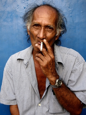 man: Old asian man smoking a cigarette