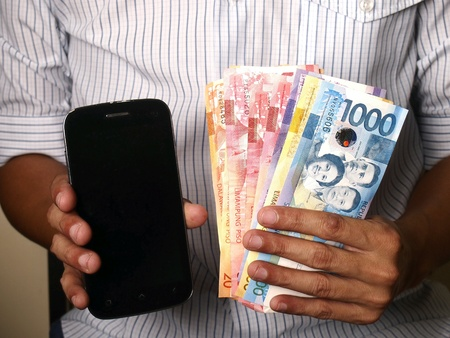 man: Man holding smartphone or cellphone and money