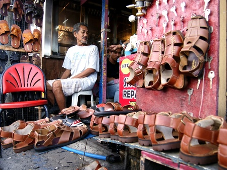 industry: Man selling handcrafted leather slippers and sandals Stock Photo