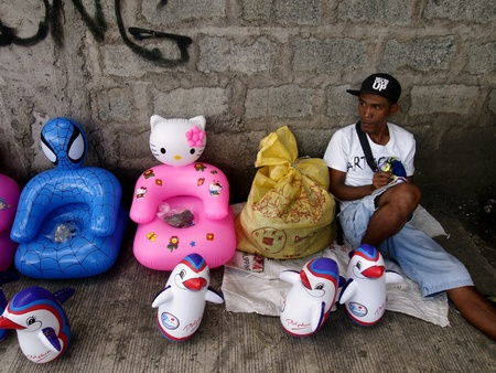 man: Man selling rubber inflatable toys at a sidewalk
