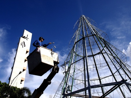 filipino adult: Man works on a giant christmas tree in antipolo city philippines