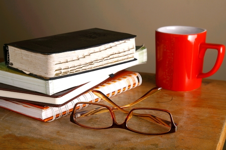 pile of books: Eyeglasses, coffee mug and pile of books
