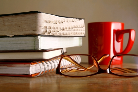 Eyeglasses, coffee mug and pile of books