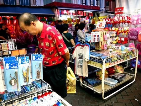 pillows: Tourists choose from a variety of souvenir products in a store in Chinatown in Singapore Stock Photo