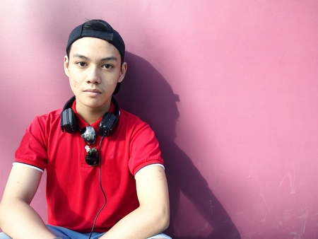 Portrait of a teen with a cap on and ear phones