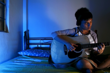 riff: Teenage boy playing with a guitar on a bed