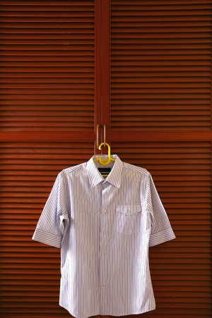 slacks: Polo shirt hanging by a clothes cabinet door