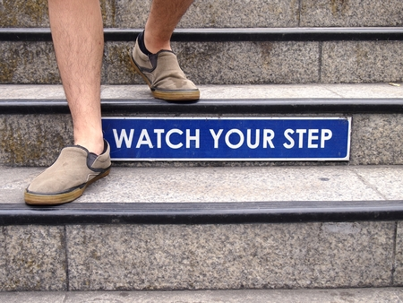 Watch your step sign on a staircase and a pair of feet with shoes