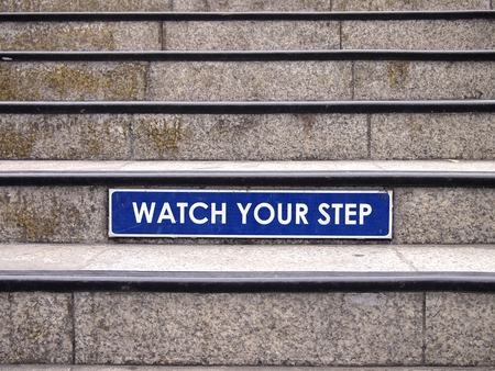 Watch your step sign on a staircase