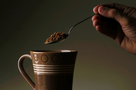 granule: Hand holding a spoon with coffee granule on it and a ceramic mug