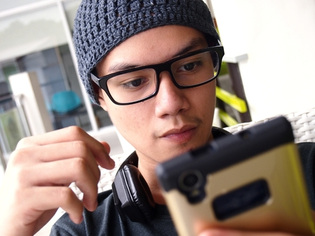 Teenager wearing a bonnet and eyeglasses using a smartphone Stok Fotoğraf