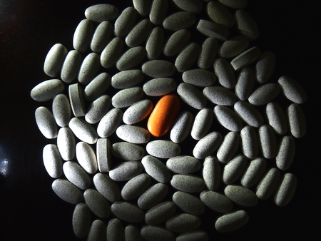 Lone orange colored pill among a bunch of white pills