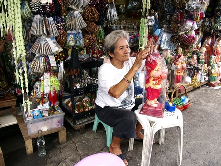 sidewalk sale: Lady fixes up a Child Jesus figurine which she sells at her store