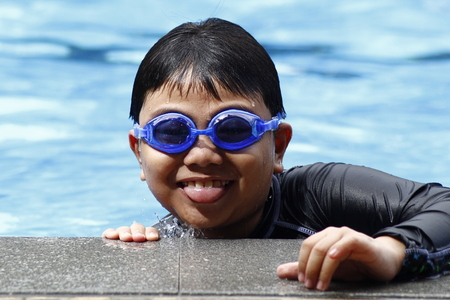 Young boy with swimming goggles in a swimming pool. Imagens