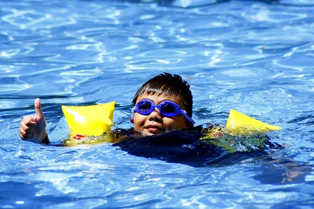 floaters: Young kid giving the thumbs up sign while swimming in a swimming pool.