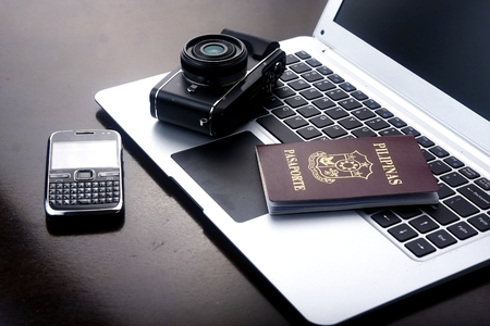 Camera, passport and cellphone on a laptop computer keyboard.
