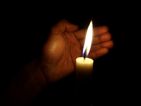 Hand covering flame of candle from wind Stok Fotoğraf