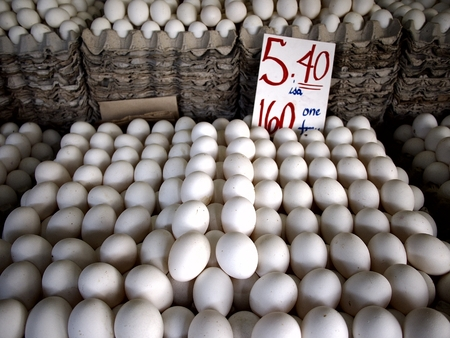 Stacks of trays of eggs on sale at a public market