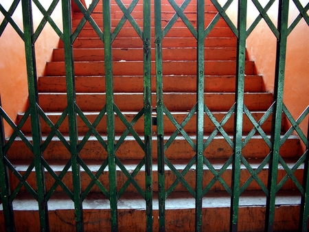 Closed green metal gate and a staircase