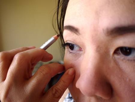 nose close up: Photo of a woman using eyebrow pencil on her eyebrows Stock Photo