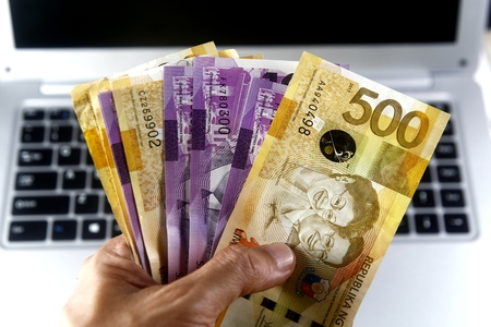Hand holding money and a laptop computer