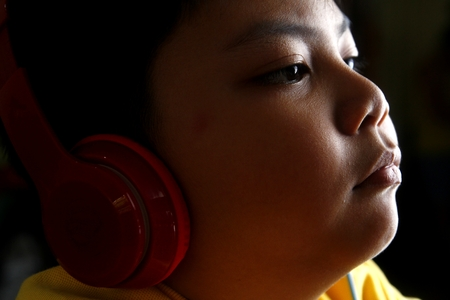 Young Asian boy with headphones Stock Photo