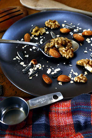 Photo of walnut, almond, oats and sunflower seeds on a plate