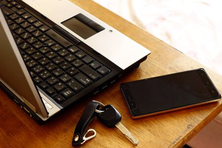 Photo of a laptop computer, car key and smartphone on a table inside a bedroom Archivio Fotografico