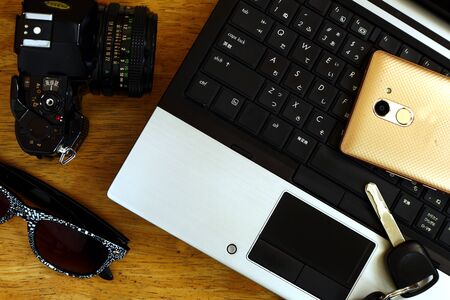 Photo of a laptop computer, manual camera, car key, sunglasses and smartphone on a table inside a bedroom