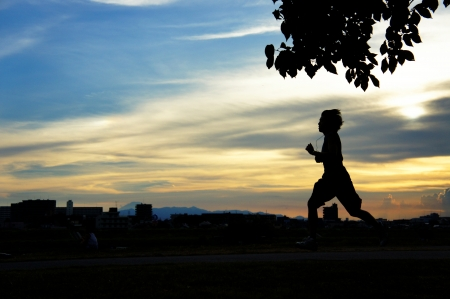 young man running in front of a sunset photo