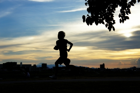 young man running in front of a sunset Stock Photo