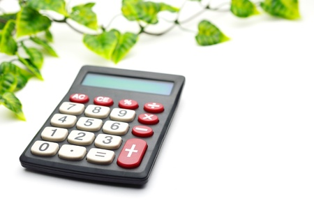 Calculator with leaf isolated on white background photo