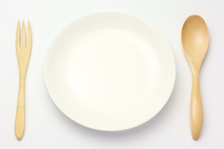 Plate and spoon on white background