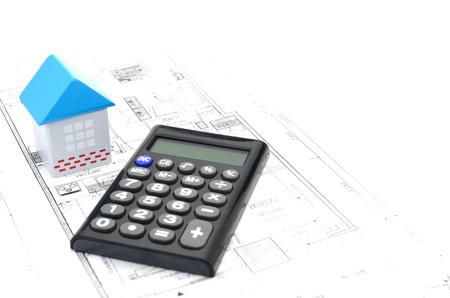 Model house and calculator on construction plan photo