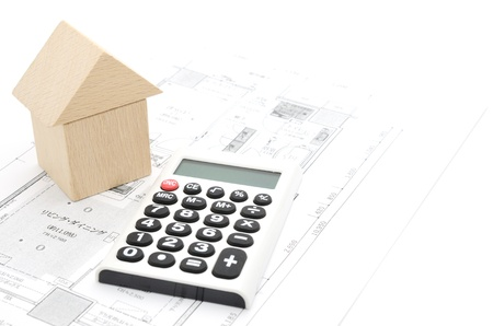 mortgage rates: Model house and calculator on construction plan