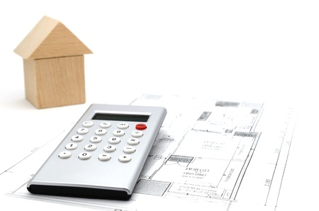 Model house and calculator on construction plan