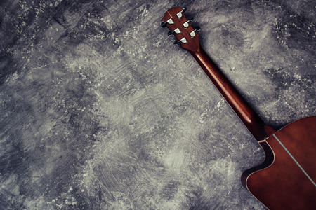 Acoustic guitar resting against a background with copy space