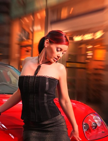 Beautiful young woman and a red sports car. photo