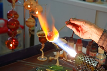 The master heats up the glass. Focus is on the hot ball the hand rotates a glass rod.