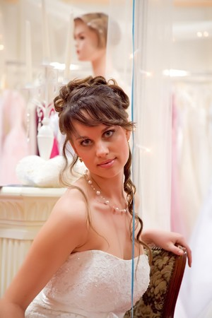 Pretty, young woman in a white wedding gown. photo