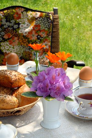 Cups of tea and simple food on a table in a garden. photo