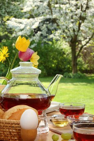 Tea and simple food on a wooden table in the garden. photo