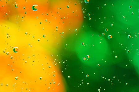 Gotas de agua sobre una zona verde, fondo amarillo.
