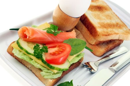 Toasts with salmon, cheese and vegetables. photo