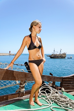 female pirate: Blond girl looking at the sailing ship.