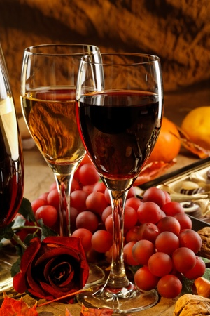 Red and white wine, fruits and rose. photo