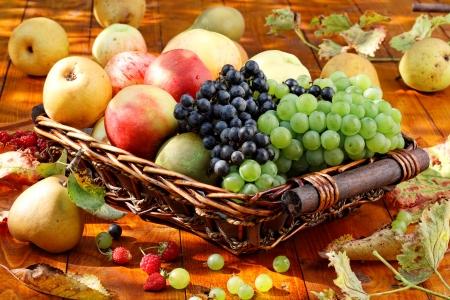 fruitmand: Mand met rijpe vruchten op de tafel. Stockfoto