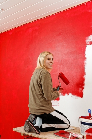 Girl painting living room in a red color. photo